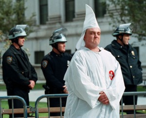 A Ku Klux Klan member (R) stands with heavy police protection during a rally in New York 23 October 1999. A crowd of several hundred anti-Klan protesters jeered the 18 robed and hooded Klansmen who made up the rally, which was permitted after a court ruled the KKK needed to remove their masks in order to proceed with the event.   AFP PHOTO/Doug KANTER        (Photo credit should read DOUG KANTER/AFP/GettyImages)